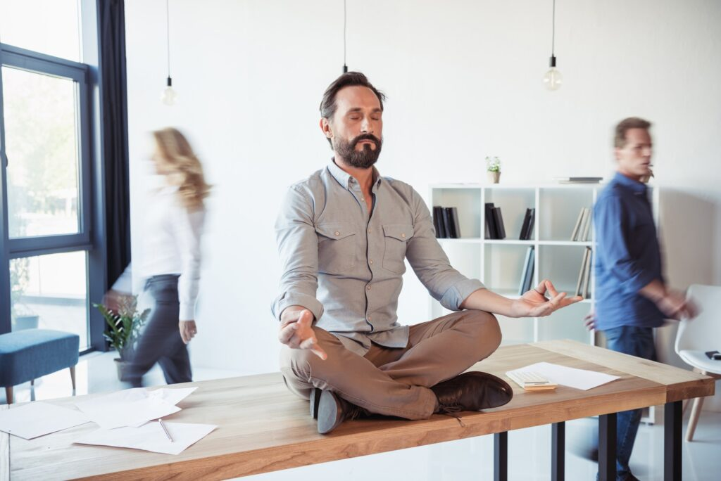 Relaxed businessman meditating in lotus position while coworkers moving in office
